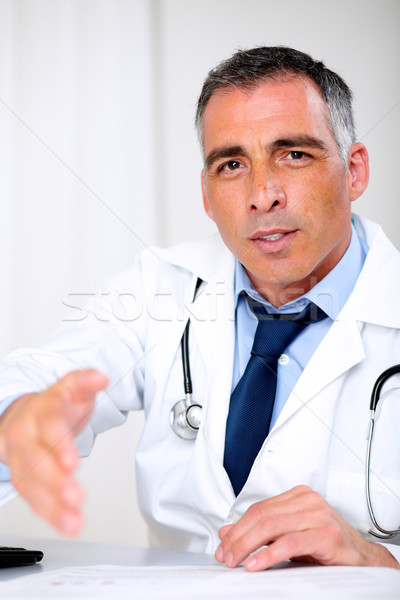 Latin doctor greeting at the consultation desk Stock photo © pablocalvog