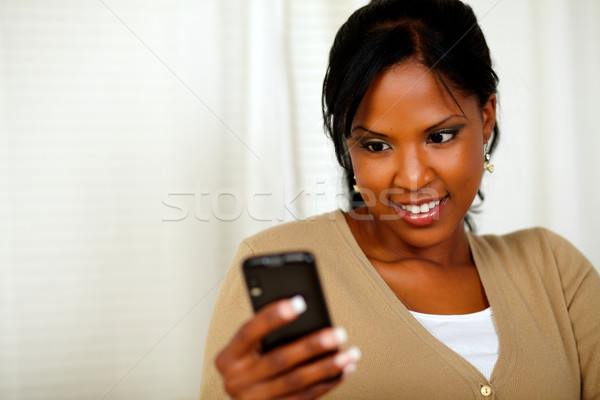 Stock photo: Pretty woman reading a text message by the mobile