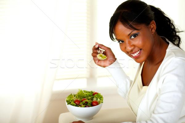 Smiling pretty woman eating green salad Stock photo © pablocalvog