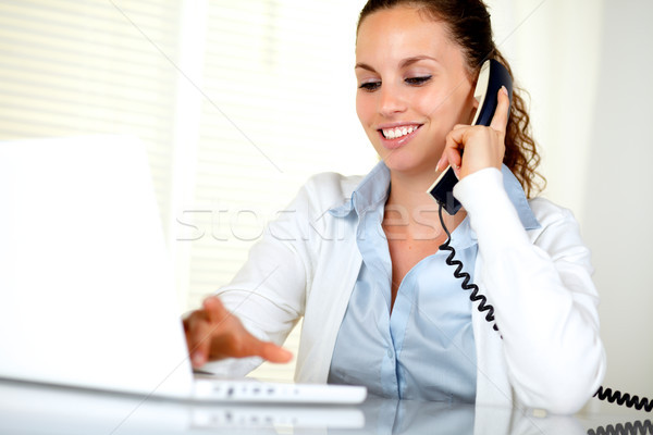 Stock photo: Smiling young woman conversing on phone