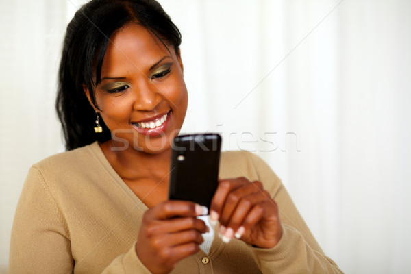 Attractive black woman sending a text message Stock photo © pablocalvog