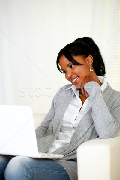 Stock photo: Lovely young woman smiling and looking to laptop