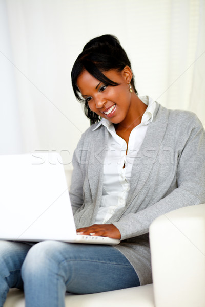 Stock photo: Pretty young woman smiling and looking to laptop