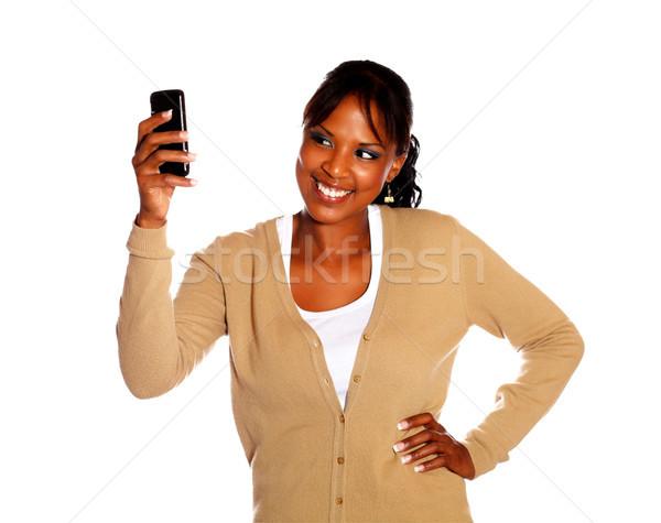 Etnik genç kadın mesaj cep telefonu beyaz Stok fotoğraf © pablocalvog