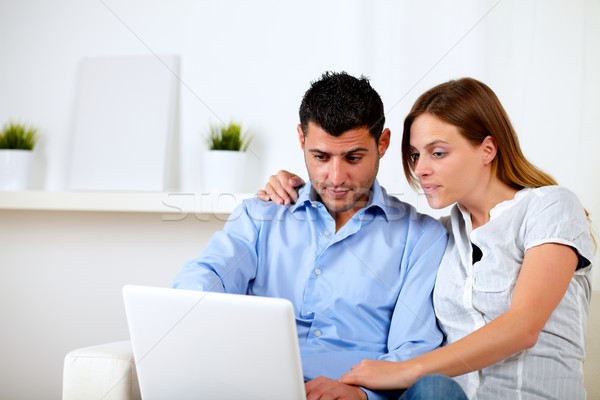Interested couple browsing on laptop Stock photo © pablocalvog