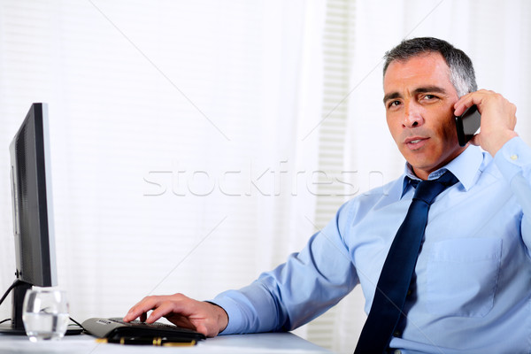 Hispanic professional man conversing on mobile Stock photo © pablocalvog