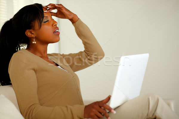 Tired woman with headache browsing the Internet Stock photo © pablocalvog