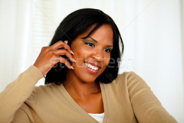 Afro-american woman conversing on mobile phone Stock photo © pablocalvog