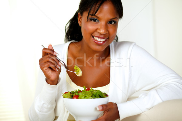 Smiling young woman looking and enjoying salad Stock photo © pablocalvog