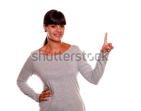 Stylish young female looking at you pointing up Stock photo © pablocalvog