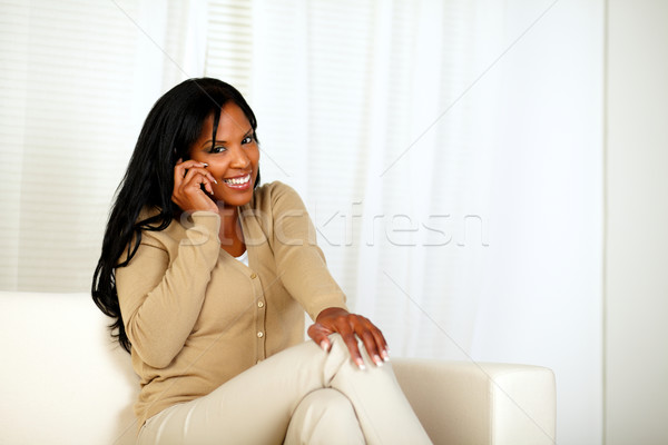 Young woman smiling at you while speaking on phone Stock photo © pablocalvog