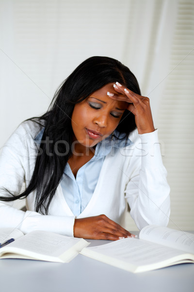 Stock photo: Beautiful student with headache browsing a book