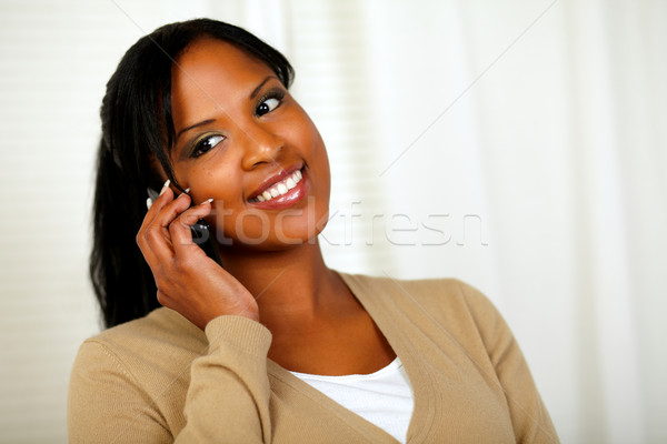 Stock photo: Smiling young woman talking on cellphone