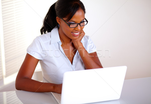 Charming young black woman working on laptop Stock photo © pablocalvog