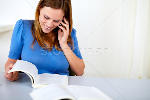 Lovely pretty woman speaking and browsing a book Stock photo © pablocalvog
