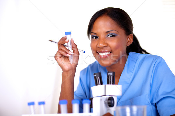 Scientific woman looking at you holding test tube Stock photo © pablocalvog