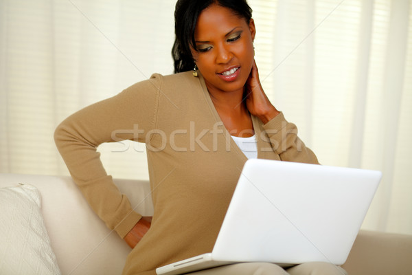 Young woman with back pain working on laptop Stock photo © pablocalvog