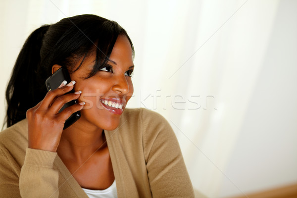 Afro-american young woman conversing on cellphone Stock photo © pablocalvog