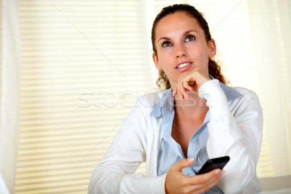 Tükröződő fiatal nő felfelé néz mobiltelefon mosolyog üzlet Stock fotó © pablocalvog