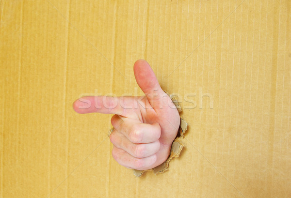 hand pointing with index finger against a cardboard background Stock photo © Pakhnyushchyy