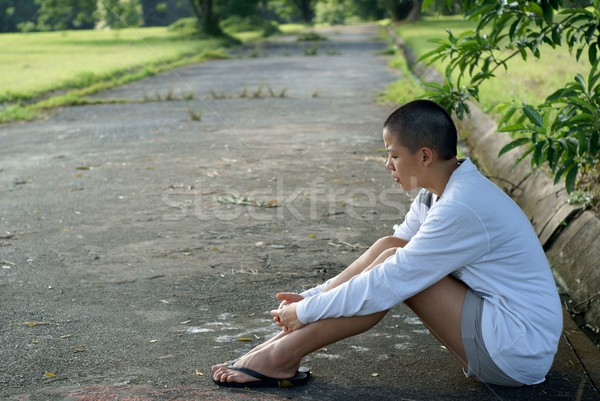 Sad bald asian woman seated on ground outdoors Stock photo © palangsi