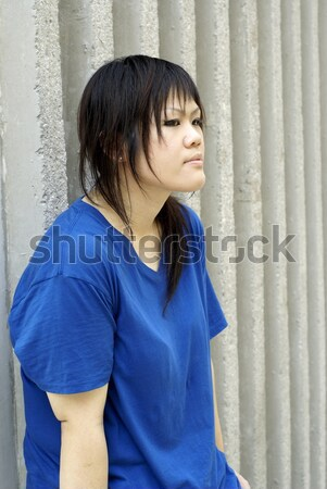Stock Photo Young Asian Teen Girl Seated Looking Up With Urban Wall
