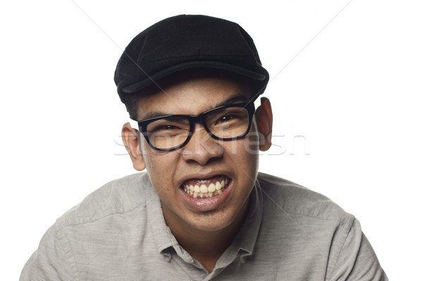 Fierce malay man showing gritted teeth wearing black cap and spectacles with white background. Stock photo © palangsi