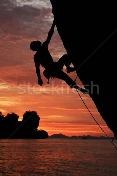 Rock silhouet klimmen klif zonsondergang oceaan Stockfoto © pancaketom