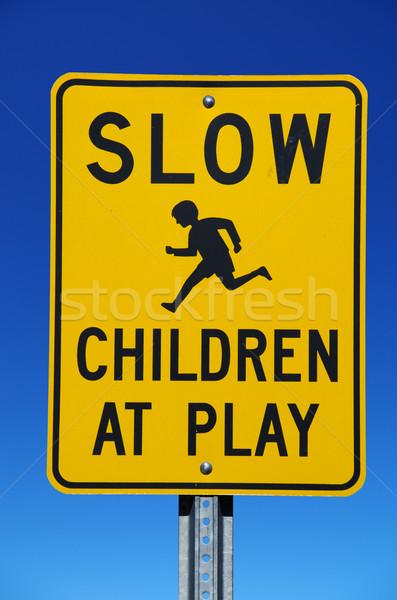 Yavaş çocuklar oynamak imzalamak sokak işareti mavi gökyüzü Stok fotoğraf © pancaketom