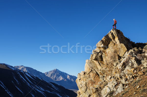 Man On Peak Looking At Mountains Stock photo © pancaketom
