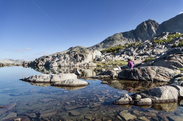 Woman Sitting By Still Mountain Lake Stock photo © pancaketom