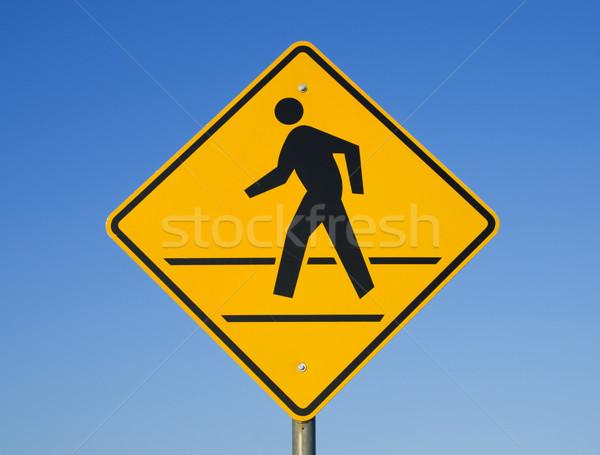 Przejście dla pieszych podpisania człowiek spaceru żółty Błękitne niebo Zdjęcia stock © pancaketom