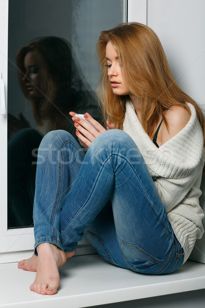 Beautiful long-haired girl, sitting on a window-sill Stock photo © pandorabox