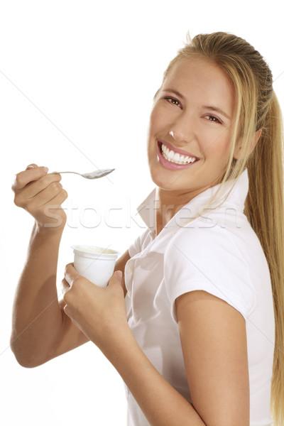 Genç kadın yeme yoğurt beyaz kadın gülümseme Stok fotoğraf © paolopagani