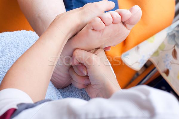 Nurse massaging foot of a patient Stock photo © Pasiphae