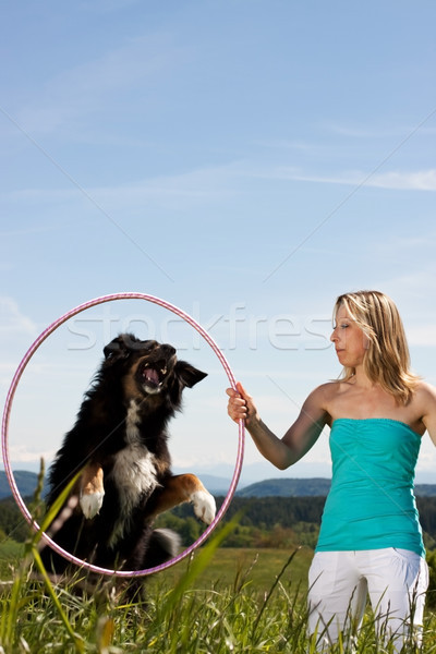 Blonde woman holding hula hoop and dog jumps through Stock photo © Pasiphae
