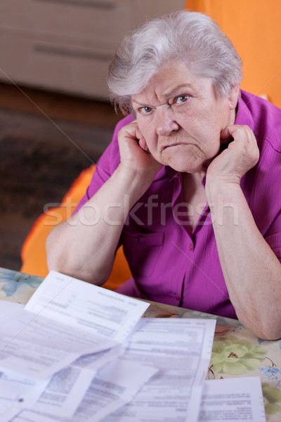 Elderly woman sits in front of papers and desperate Stock photo © Pasiphae