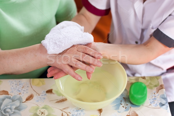 Stock photo: nurse washes old patient's hands