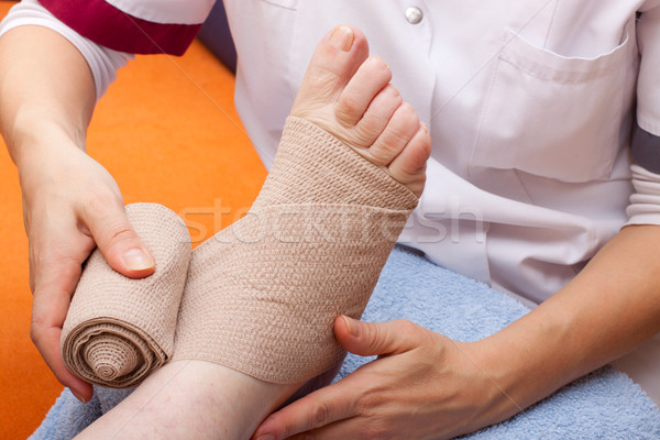 Doctor bandaged foot of a patient Stock photo © Pasiphae