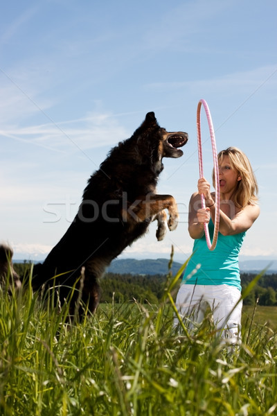 young blond woman holding hula hoop and dog jumps through Stock photo © Pasiphae