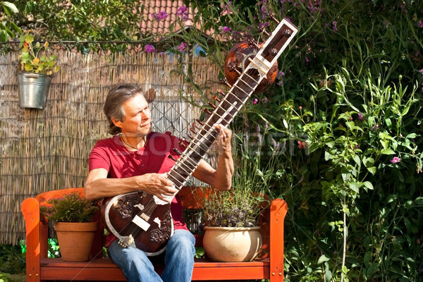 Elderly man sitting in his garden and playing a sitar Stock photo © Pasiphae