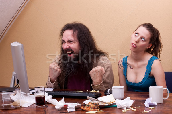 Man celebrating success on pc, woman rolling her eyes Stock photo © Pasiphae