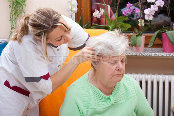 Nurse massages the head of a senior Stock photo © Pasiphae