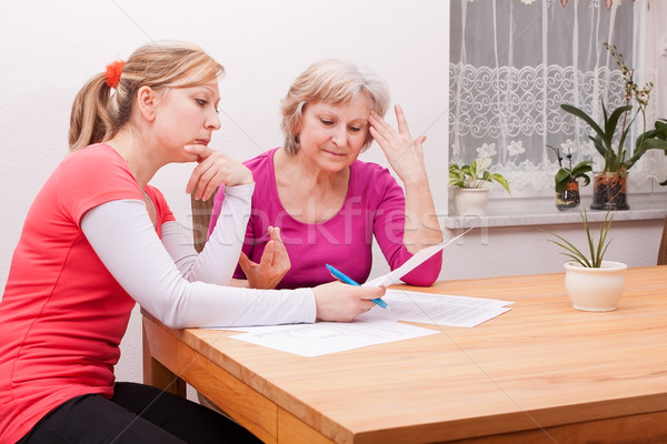 Two women pondering over documents Stock photo © Pasiphae