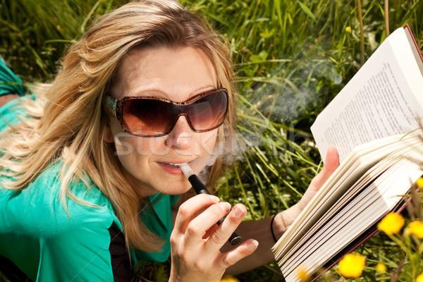 Jovem loiro mulher elétrico cigarro leitura Foto stock © Pasiphae