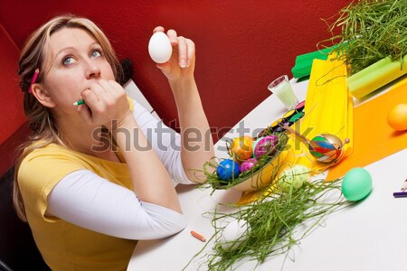 Blonde woman with an easter egg is thinking Stock photo © Pasiphae