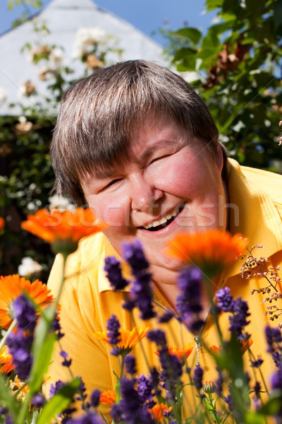 disabled woman lying on grass and smell on flowers Stock photo © Pasiphae