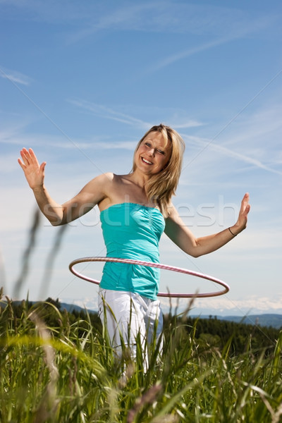 Blond young mature woman exercises with hula hoop Stock photo © Pasiphae