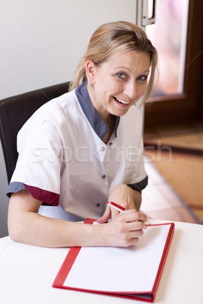 Geriatric nurse makes  notes about a patient Stock photo © Pasiphae