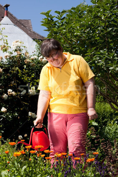 disabled woman waters flowers in the garden Stock photo © Pasiphae